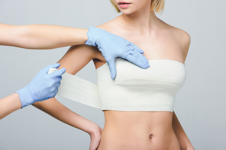 cropped view of plastic surgeon wrapping female breast with bandage, isolated on grey