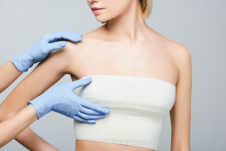 cropped view of plastic surgeon in latex gloves checking female breast in bandage, isolated on grey Stock Photo