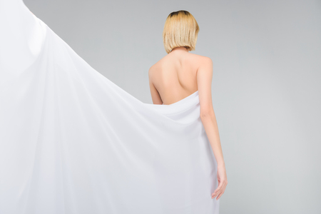 back view of naked girl posing in elegant white veil, isolated on grey Stock Photo