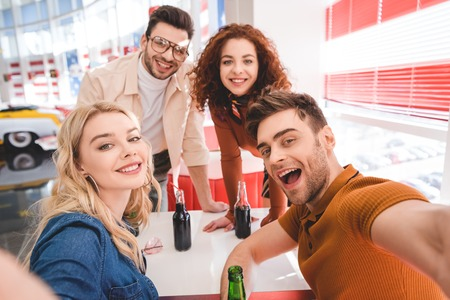 selective focus of smiling  handsome and attractive friends holding glass bottles with soda and beer