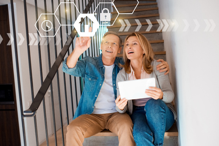 man pointing hand and woman holding digital tablet while sitting on stairs, smart home concept
