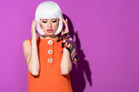 Pensive girl touching white wig and looking down on purple background