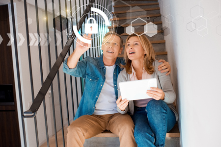 smiling man pointing hand and wife holding digital tablet while sitting on stairs, smart home concept