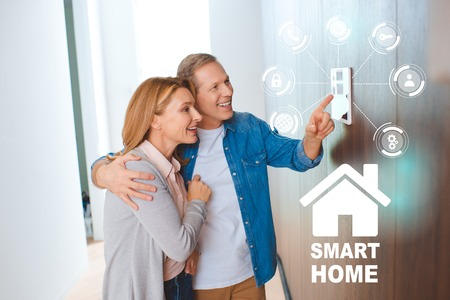 happy husband hugging wife while pointing at smart house system control panel
