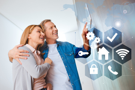 smiling husband hugging happy wife while pointing at smart house system control panel