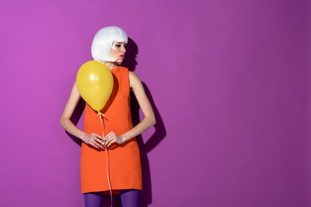 Girl in white wig holding yellow air balloon on purple background