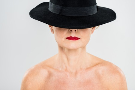middle aged elegant and fashionable woman with red lips in black hat isolated on grey