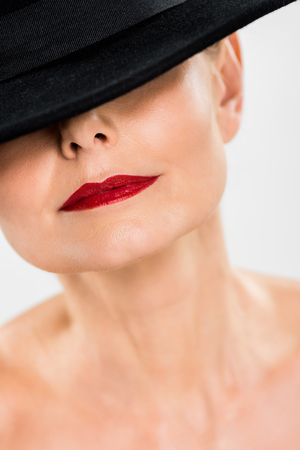 selective focus of middle aged elegant and fashionable woman with red lips in black hat isolated on grey Stock fotó