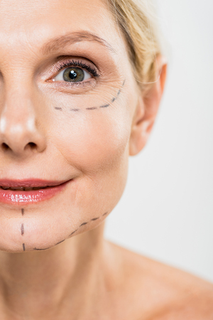 selective focus of middle aged woman with lines on face isolated on grey