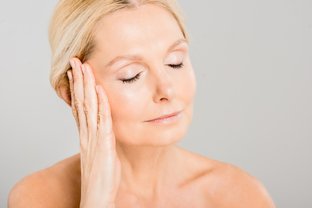 attractive and blonde mature woman with closed eyes touching her face isolated on grey