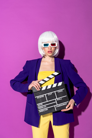 Young woman in 3d glasses holding clapperboard on purple background Stockfoto