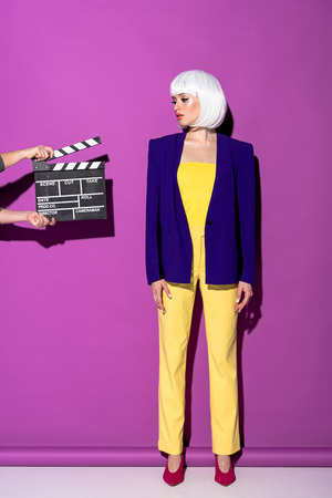 Full length view of young woman in white wig standing on purple background
