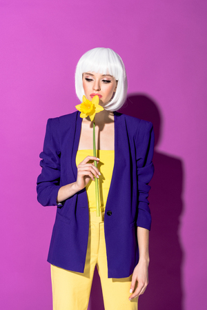 Pensive girl in white wig sniffing flower on purple background Imagens - 119964175