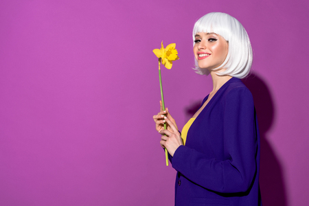Inspired girl in white wig holding flower and smiling on purple background Stock Photo