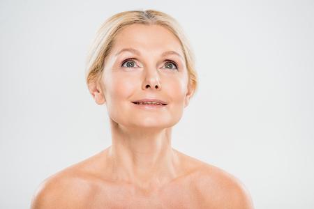 Atractiva y rubia mujer madura mirando hacia arriba sobre fondo gris