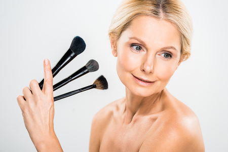 beautiful and blonde mature woman looking away and holding cosmetic brushes on grey background