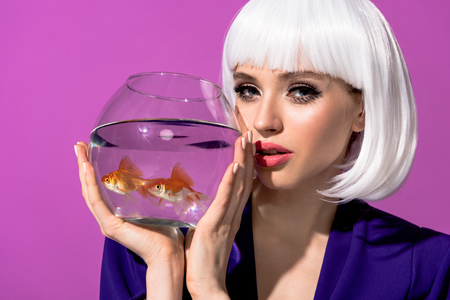 Charming young woman in white wig holding aquarium with goldfishes isolated on purple Фото со стока
