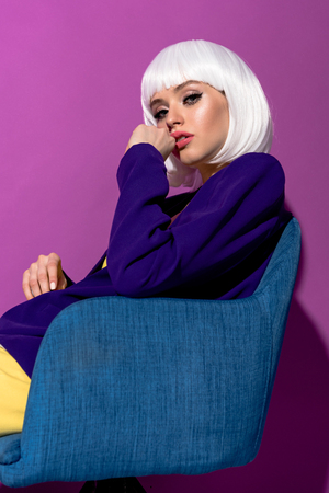 Interested young woman in white wig sitting in armchair on purple background