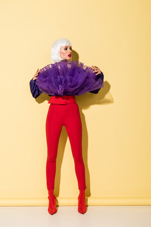 Fashionable girl in red pants looking away on yellow background