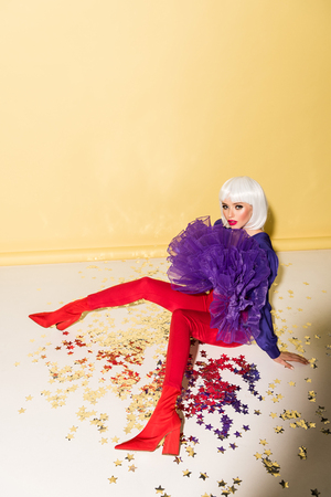 Charming young woman in white wig sitting on confetti on yellow background