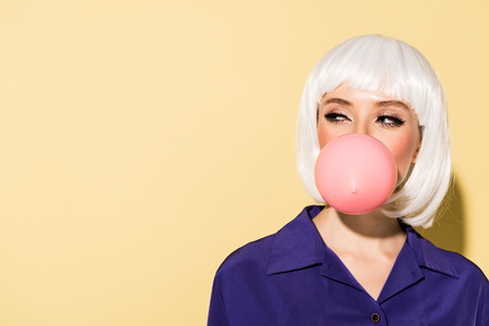 Girl in white wig chewing bubble gum on yellow background Banque d'images