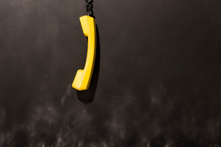 Yellow handset with black wire hanging on dark background Фото со стока - 119587279