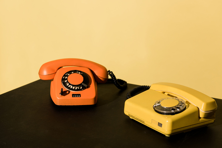 Two old telephones on black table on yellow background