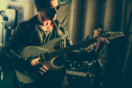 selective focus of man in sunglasses playing elecric guitar