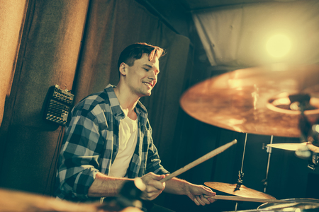 selective focus of handsome drummer holding drum sticks and playing drums