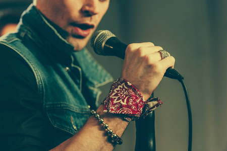 cropped view of stylish man singing in microphone