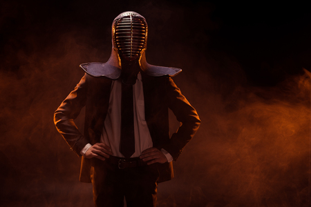 Kendo fighter in formal wear and helmet standing with arms akimbo on dark