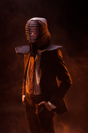 Confident kendo fighter in formal wear and helmet standing with hands in pockets on dark