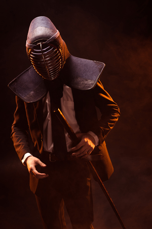 Kendo fighter in formal wear and helmet holding bamboo sword on dark