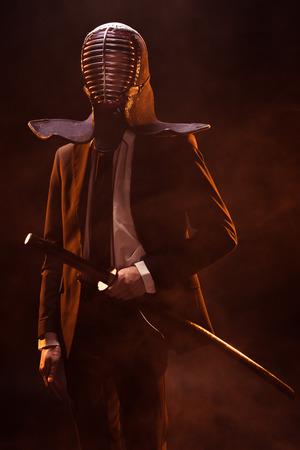 Man in formal wear and kendo helmet holding bamboo sword on dark