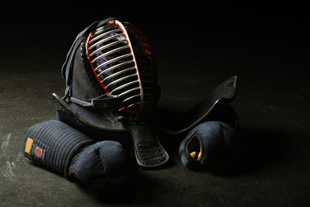 Kendo gloves and traditional helmet on dark surface