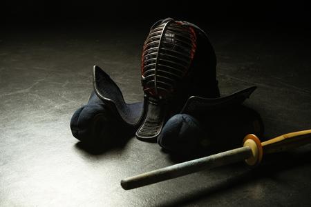 Kendo gloves, helmet and bamboo sword on dark surface Stock Photo
