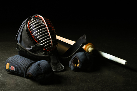 Kendo gloves, helmet and bamboo sword on dark surface Stok Fotoğraf