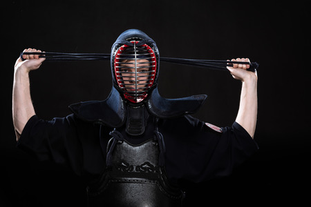 Kendo fighter in armor tying helmet on black