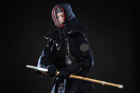 Kendo fighter in helmet holding bamboo sword and looking away on black