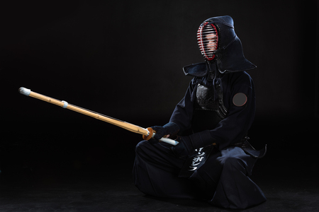 Kendo fighter in helmet holding bamboo sword on black 版權商用圖片