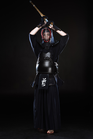 Full length view of kendo fighter in armor practicing with bamboo sword on black Banque d'images - 119966651