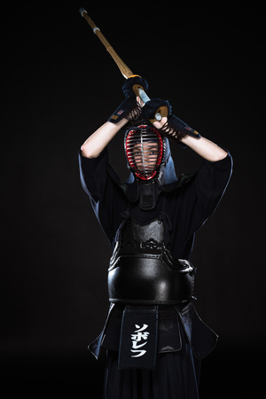 Kendo fighter in armor practicing with bamboo sword on black Banque d'images - 119966783