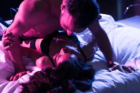 mężczyzna patrzący na namiętną kobietę na łóżku z neonowym światłem Zdjęcie Seryjne