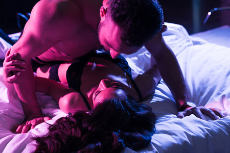 man looking at passionate woman on bed with neon light