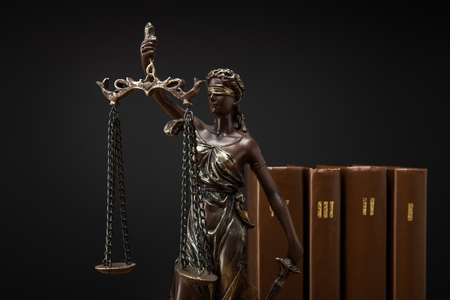 bronze statuette with scales of justice and volumes of brown books isolated on black