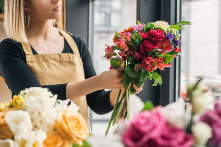 Partial view of florist making bouquet in flower shop