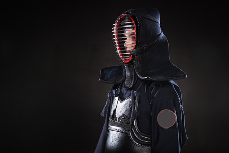 Kendo fighter in armor and traditional helmet on black Stock Photo