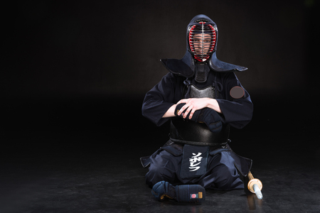 Kendo fighter in helmet sitting on floor and taking off glove on black Banque d'images - 119967212