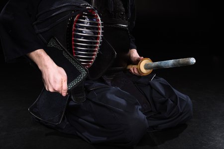Cropped view of kendo fighter holding helmet and bamboo sword on black