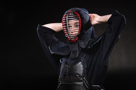 Kendo fighter in armor tying helmet and looking away on black Stok Fotoğraf